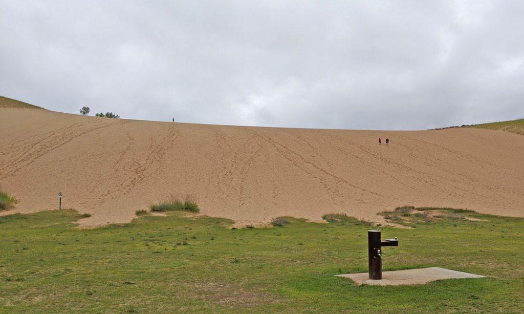 Tall sand dune under grey skies