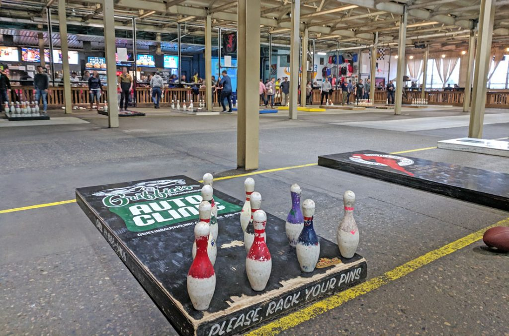 Bowling pins arranged on a wooden platform with fowling players in the background