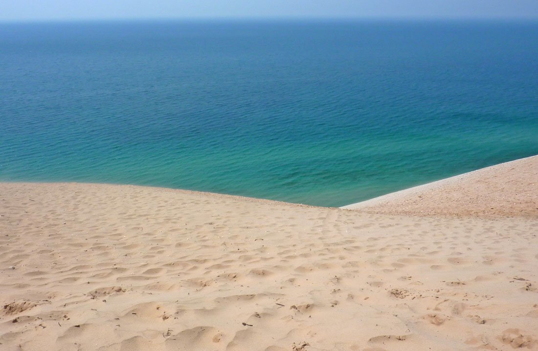 Sand dunes leading down to turquoise blue waters, on a Michigan travel blog