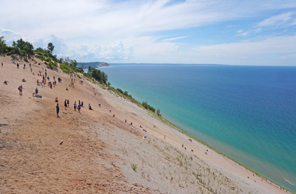 Steep sand dune dotted with visitors leading down to a large blue lake
