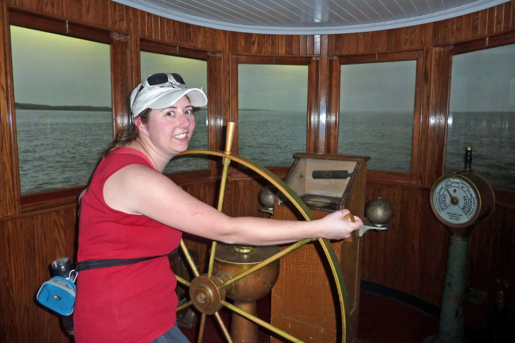 White woman in a red tank top pretending to steer a ship with a large wheel