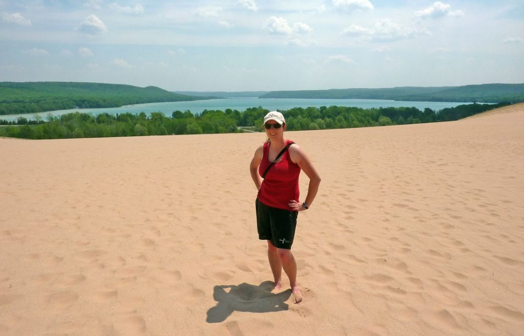 White woman in a red tank top standing on a large sandy expanse with a small lake in the background