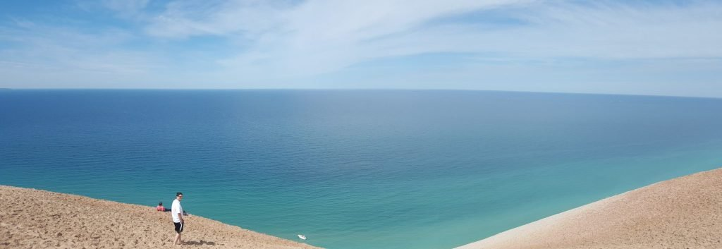 Panorama of turquoise blue waters below a large sand dune with one white man standing on the edge