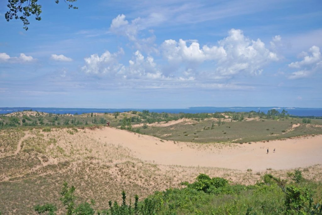 Sand dune covered with scrub grass with a large lake in the background under blue skies