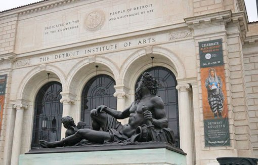 Dark metal sculpture of a reclining man in front of the arched entrance to the Detroit Institute of Arts