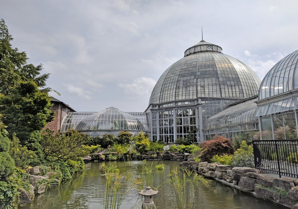 Glass domes of a conservatory on Belle Isle with plants and a small pond in the foreground, one of the top things to do in Detroit, Michigan