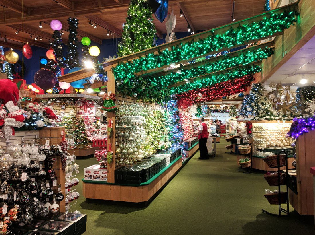 Shelves full of multi-colored Christmas ornaments with green strings of lights overhead at Bronner's Christmas Wonderland in Frankenmuth, Michigan