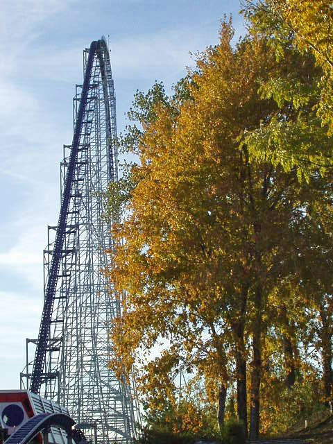 Tall arching framework of the Millennium Force, a roller coaster at Cedar Point, with colorful fall foliage along the side