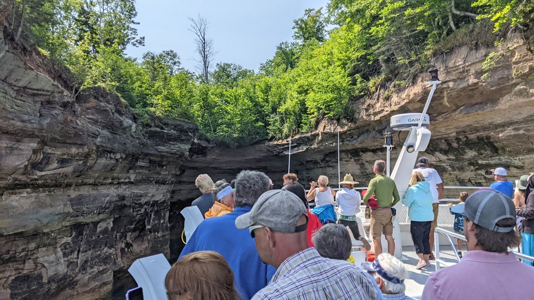 Passengers on the top deck of a Pictured Rocks tour boat inside a narrow inlet called Chapel Cove