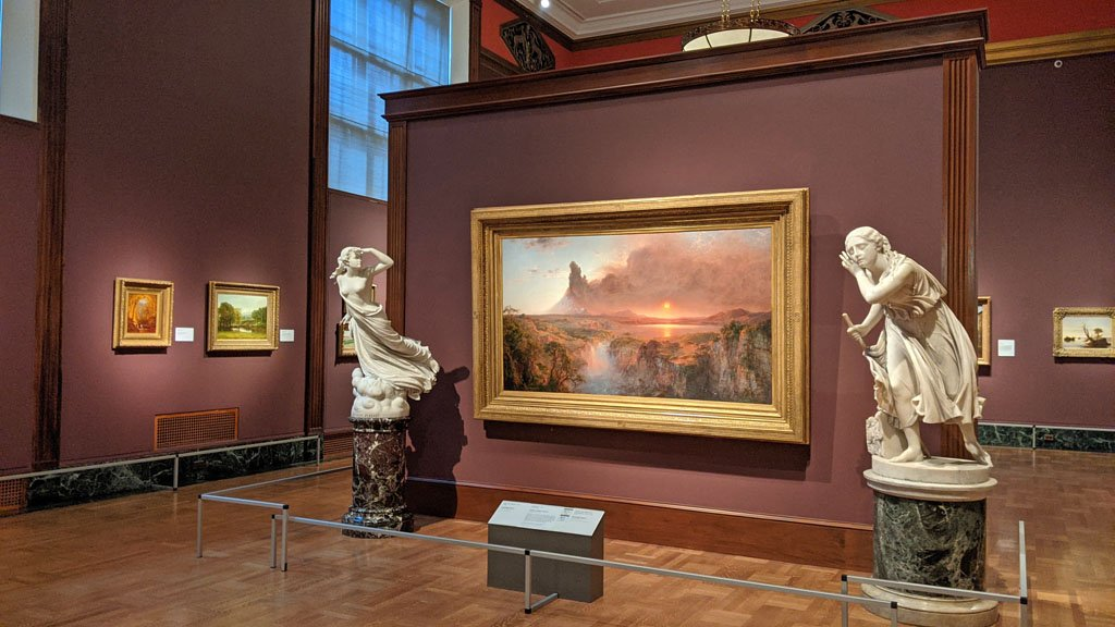 Portrait gallery with burgundy walls and various landscape paintings in the Detroit Institute of Arts