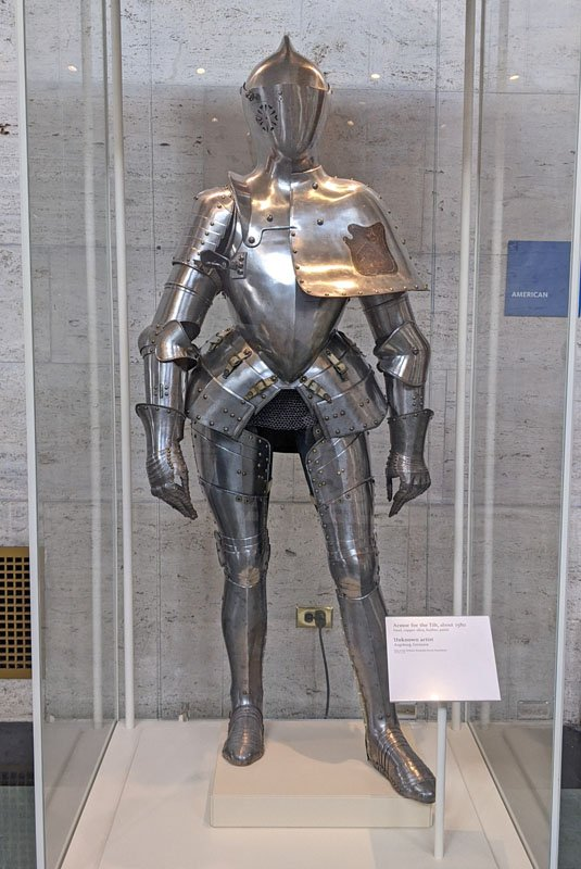 Silver suit of armor with accents of gold in a glass display case