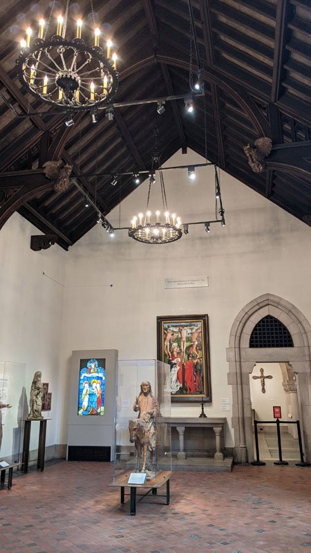 Vaulted ceiling with beams resembling a church with chandeliers and stained glass and statues on display at the Detroit Institute of Arts