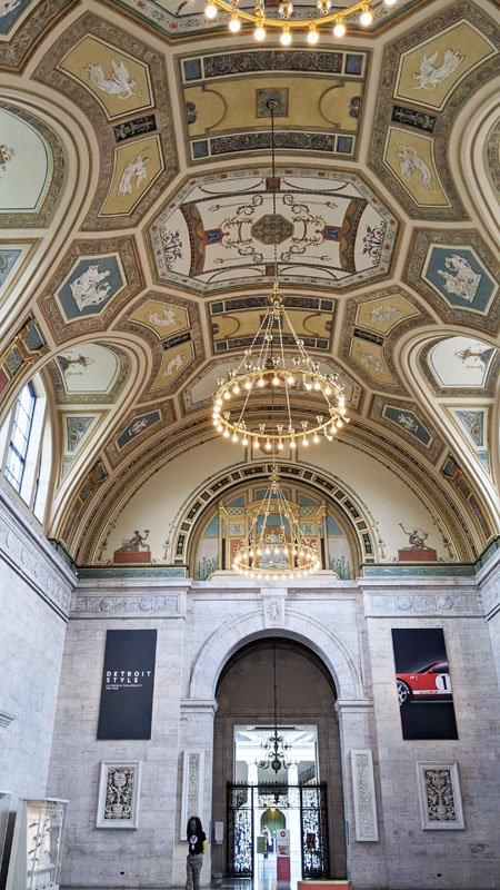 High arched ceiling with elaborate painted decor and chandeliers