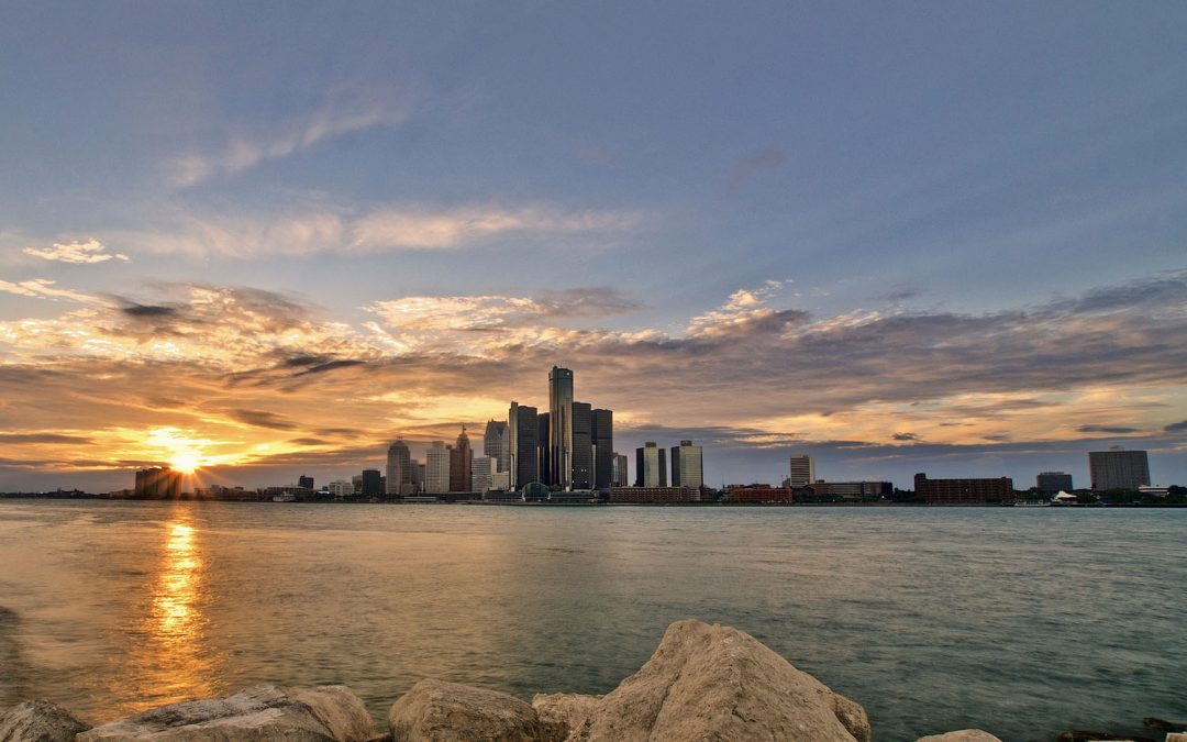 Photo of the Detroit skyline with the sun setting on the left side. Rocks and a river are in the foreground.