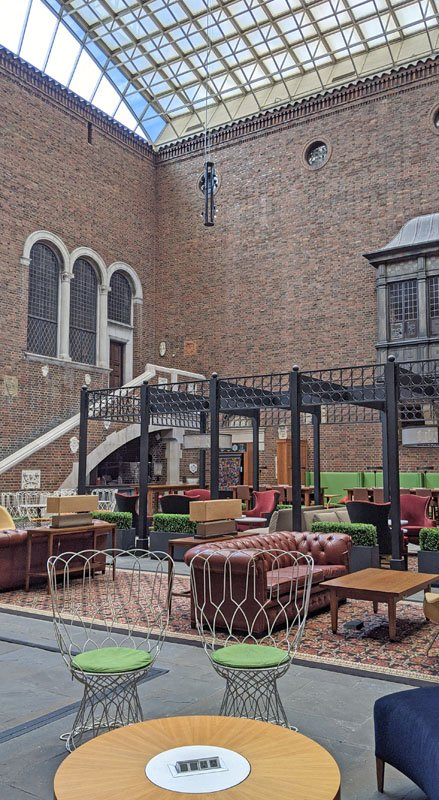 Two-story glass-roofed courtyard made of brick with colorful cafe-style furniture