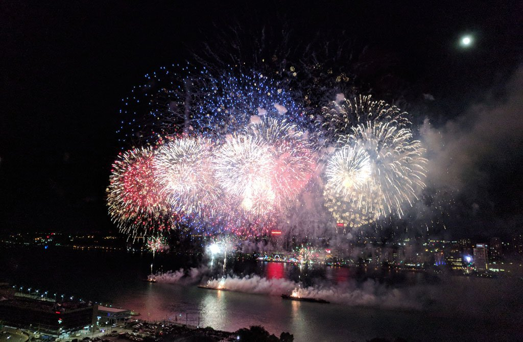 Red, white, and blue fireworks launched from barges in the Detroit River with a full moon shining in the background