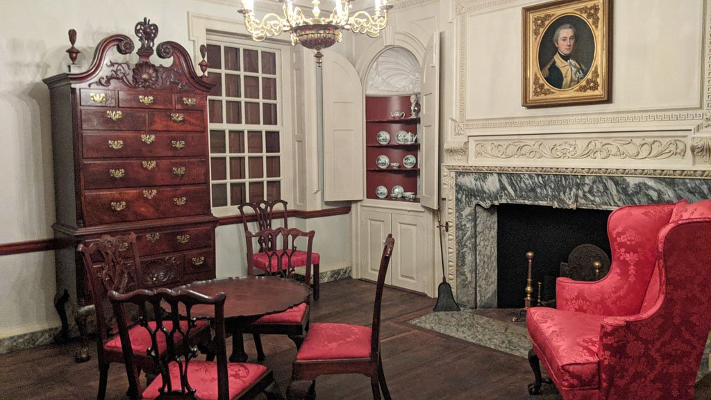 White walled reconstruction of a historic living room with red chairs and dark wooden furniture in the DIA