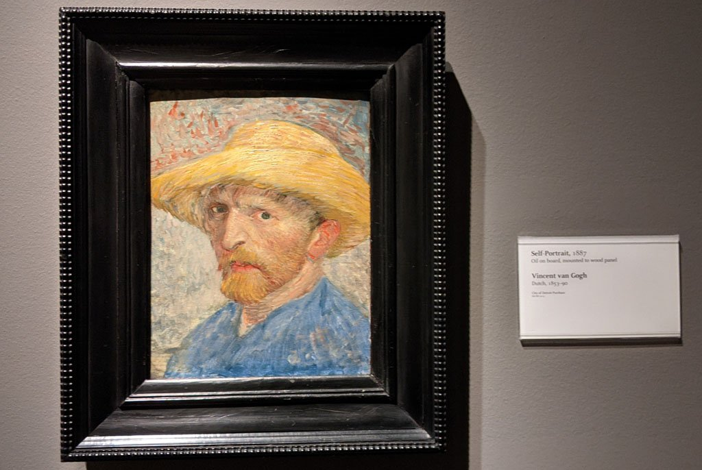 Framed painting featuring Van Gogh's self portrait in which he wears a yellow brimmed hat and blue shirt