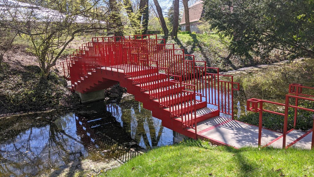 Red footbridge with geometric shapes spanning a small stream in Dow Gardens