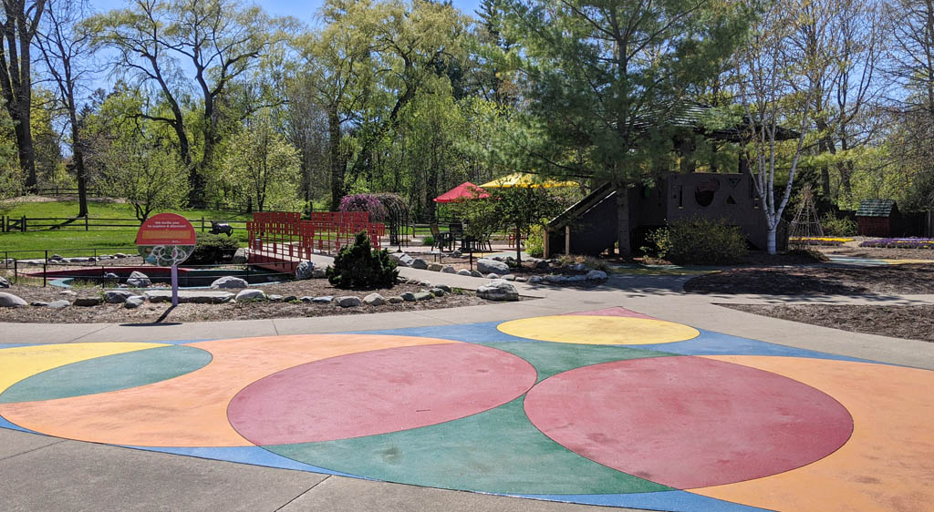 Colorfully painted cement circles with trees and signage in the background at the Dow Gardens Children's Garden