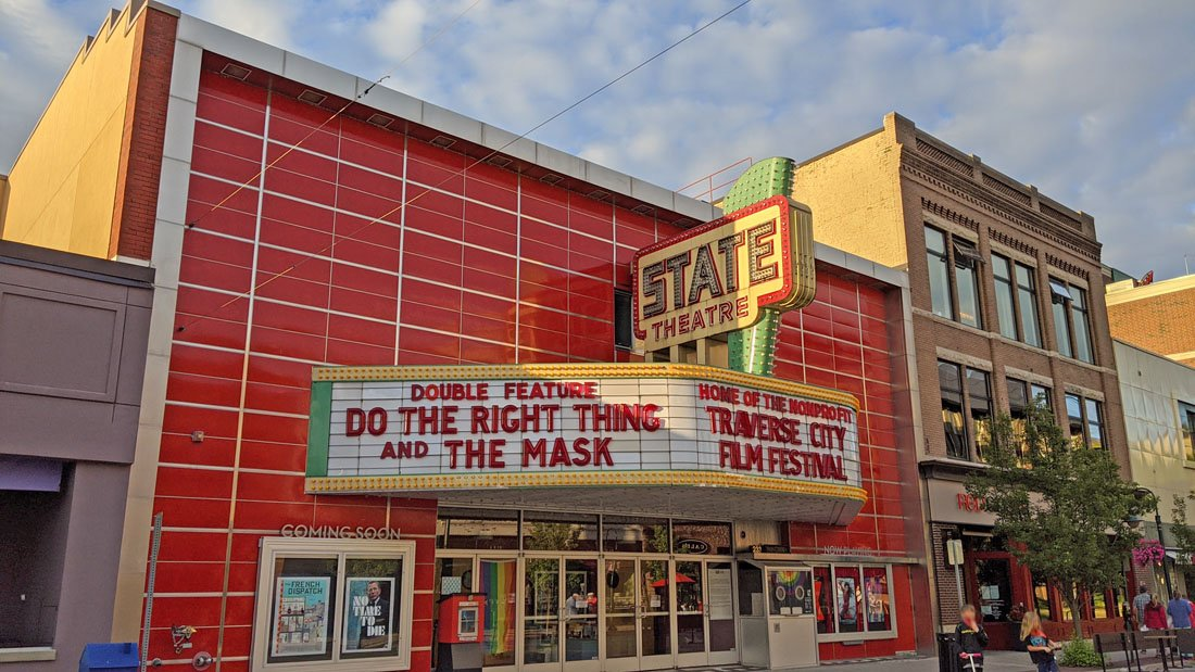 Historic movie theater with a red front and colorful marquee in downtown Traverse City