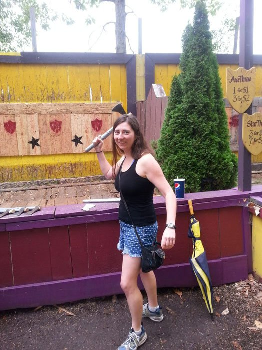 White woman in a black tank top and jean shorts posing for the camera with an axe in front of an axe-throwing target at the Michigan Renaissance Festival