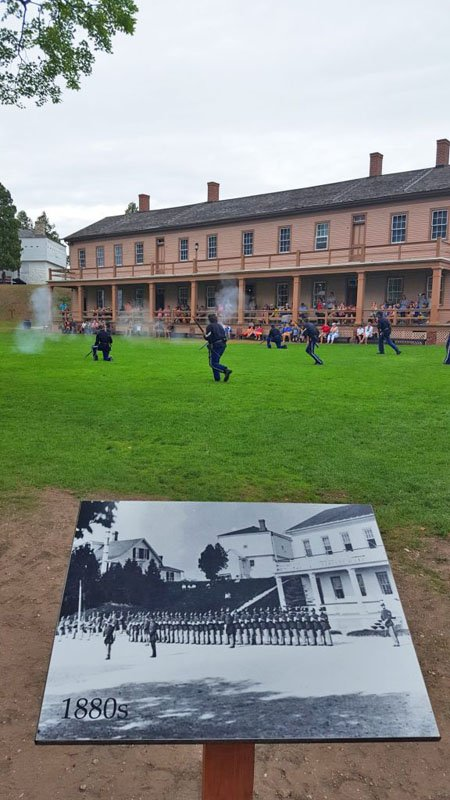 Soldiers in period costume performing battle drills on the parade grounds at Fort Mackinac