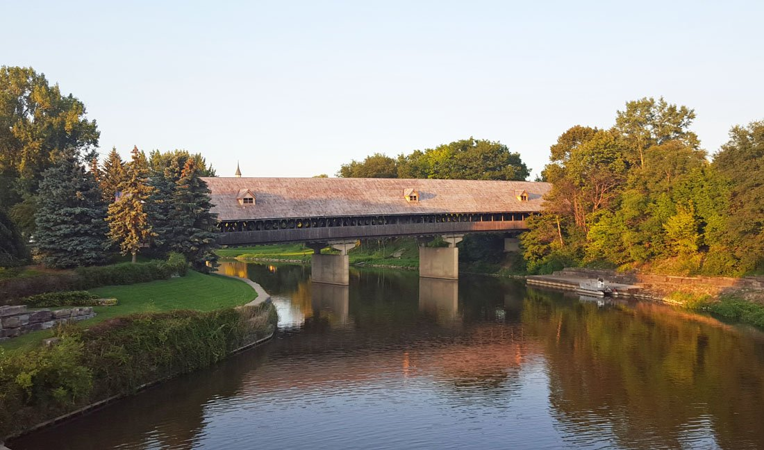 Covered wooden bridge spanning a still river with green and yellow foliage on both banks in Frankenmuth, Michigan