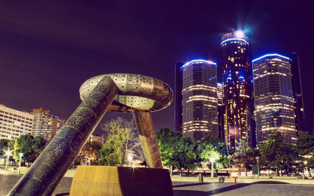 """Night time photo featuring a large abstract sculpture in Hart Plaza with the tall, cylindrical towers of the Renaissance Center in the background, with title """"Top 10 Things to Do in Detroit, Michigan"""""""