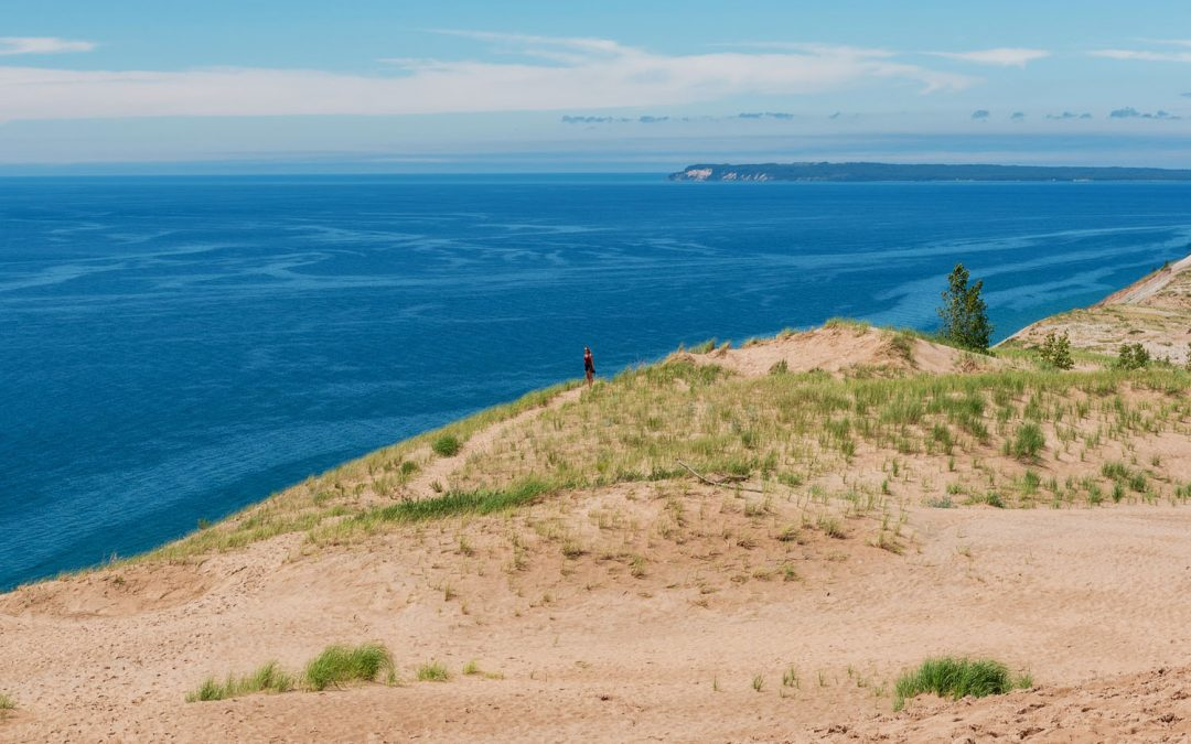 Woman standing atop a massive sand dune with bright blue waters stretching out to the horizon in Sleeping Bear Dunes, one of the top things to do in Michigan