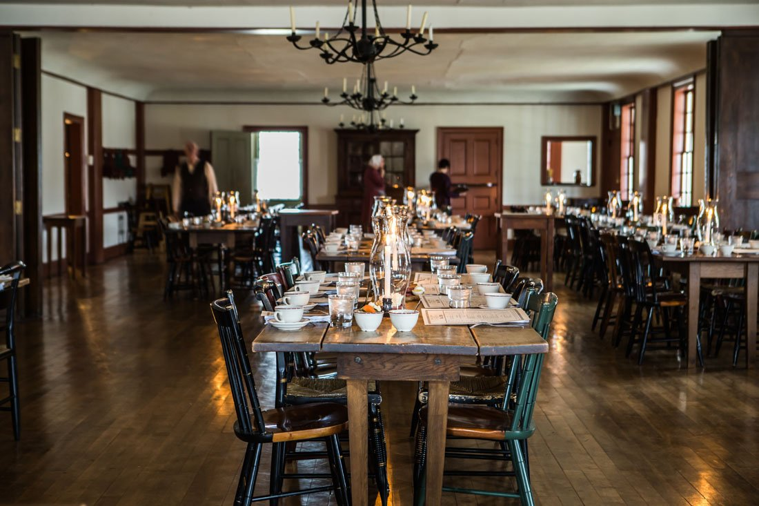 Photo of a historic dining room decorated as though it's the 1800s with wooden chairs and white linens