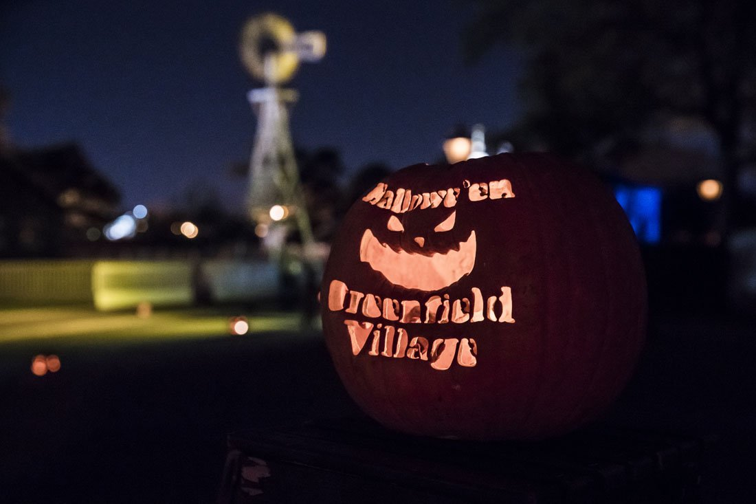"""Photo of a pumpkin with """"Hallowe'en at Greenfield Village"""" carved into it, lit by a candle with historic farm buildings in the background"""