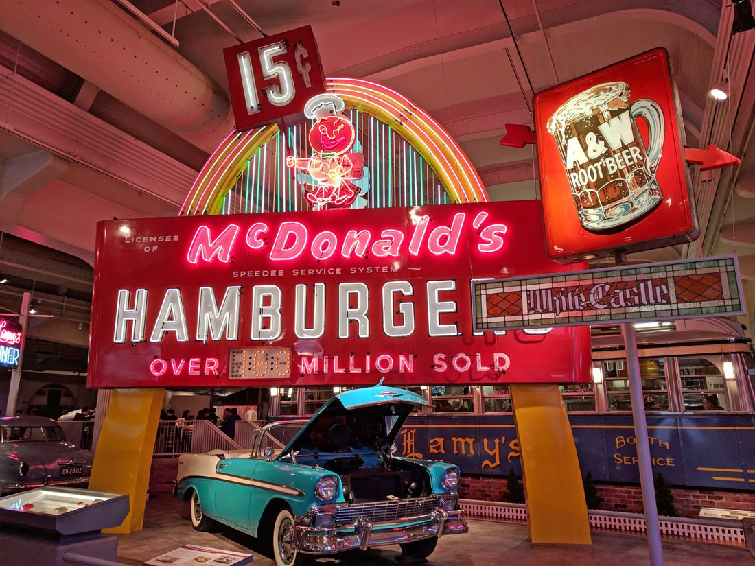 Photo of a museum display featuring a light blue classic car in front of a large old school McDonald's arch with neon lights