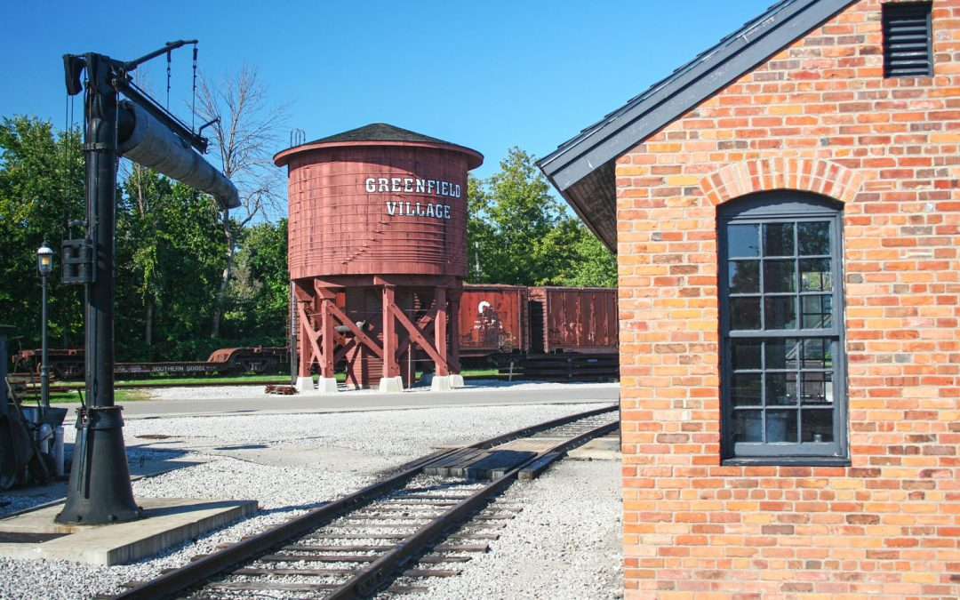 Photo of train tracks, a water tower, and a historic brick building in Greenfield Village
