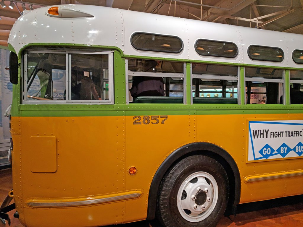 Old fashioned bus painted white, green, and yellow in the Henry Ford Museum