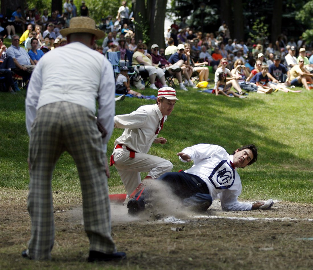 Men in historic baseball outfits making a play at home plate while a crowd of spectators watches from a hill