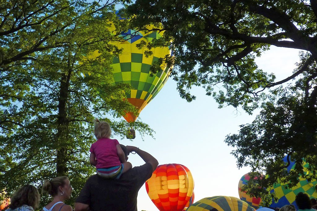 Young girl on a man's shoulders watching hot air balloons between the trees