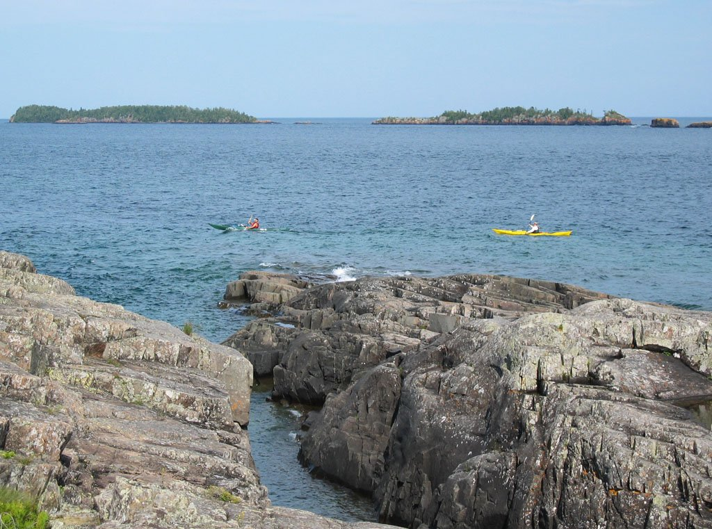 Kayakers in a large lake with boulders and rock formations in the foreground