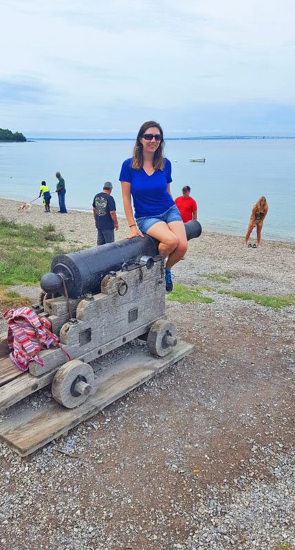 White woman posing for a photo atop a cannon at the British Landing beach on Mackinac Island