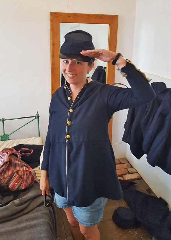 White woman saluting in a historic costume at Fort Mackinac