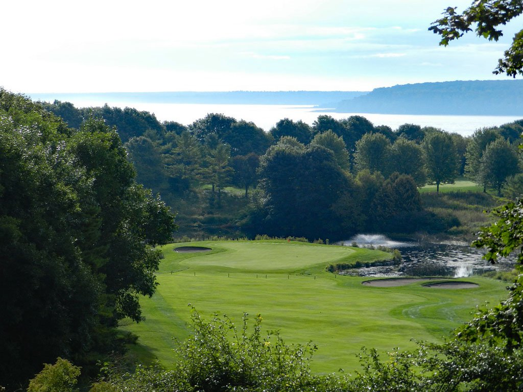 Groomed golf course hole with thick foliage and a small fountain in a water feature on Mackinac Island