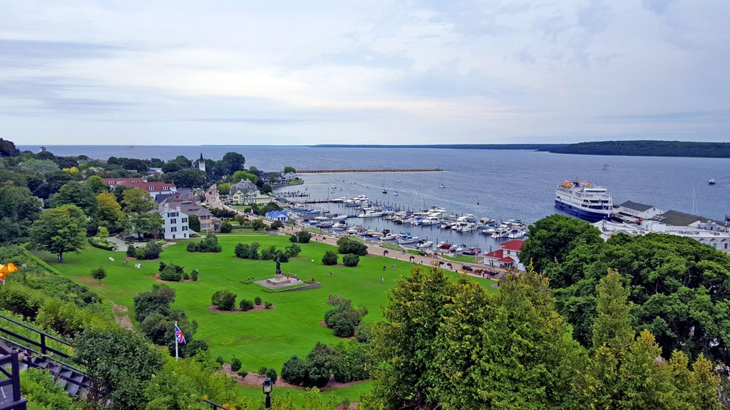 Boats lined up in a harbor with a large grassy lawn in the foreground on Mackinac Island