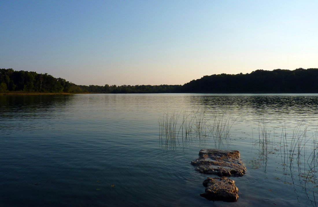 Dim skies at dusk over a small lake in the Metamora-Hadley Recreation Area