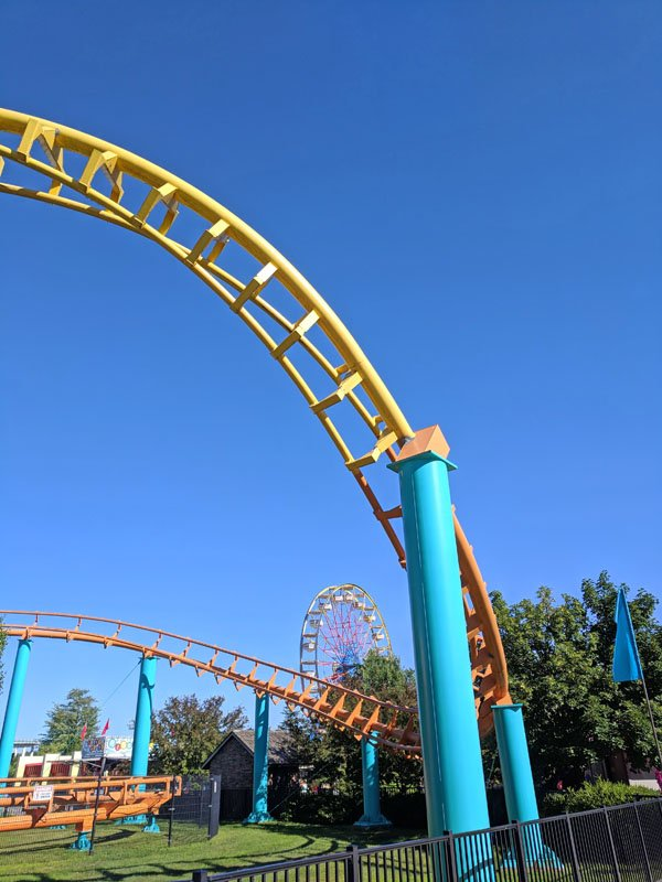 Yellow roller coaster track held up by bright blue supports twisting under clear blue skies at Michigan's Adventure