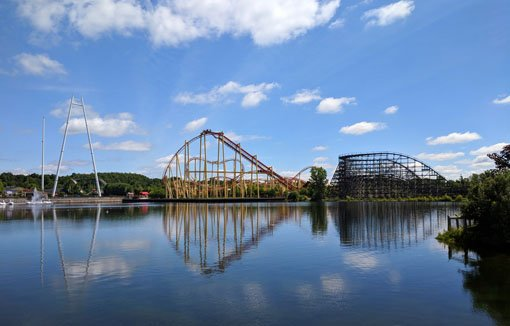 Roller coaster tracks reflected in a still pond under blue skies