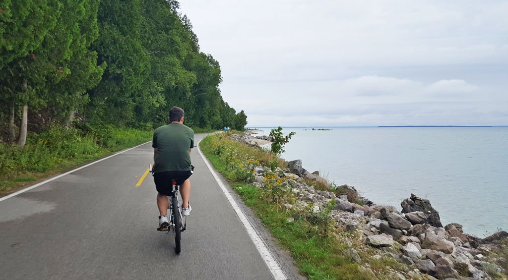 White man in a green shirt riding a bike on a paved road along the shores of Mackinac Island