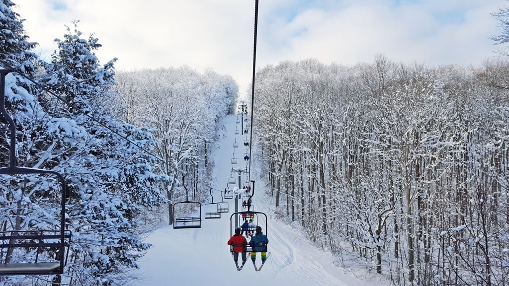 Skiers riding a chairlift up a snowy mountain surrounded by snow-covered trees