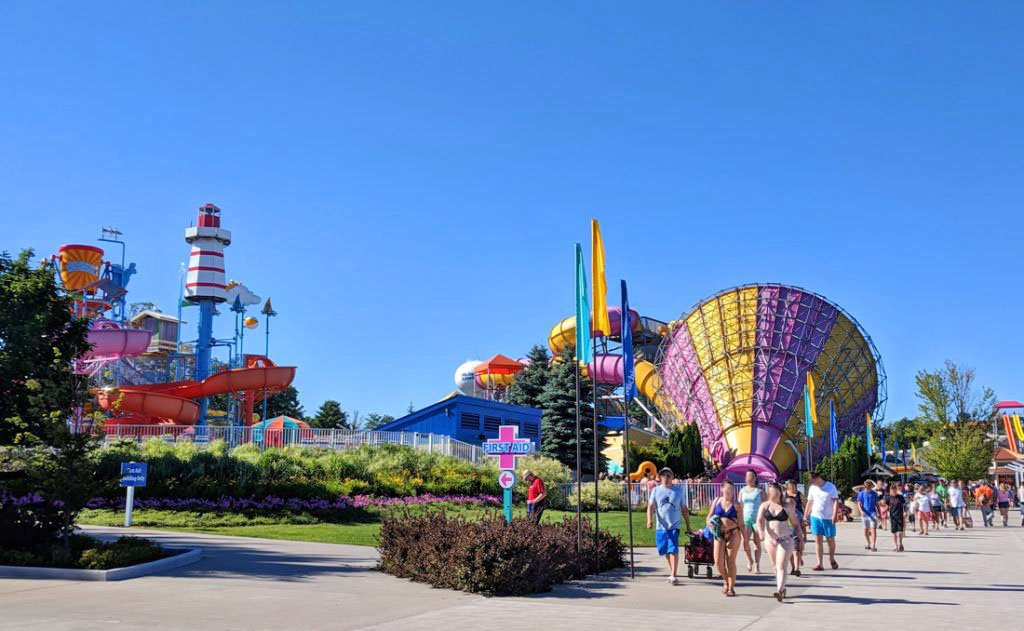 Visitors walk in front of the Michigans Adventure water park with colorful water rides in the background under clear blue skies