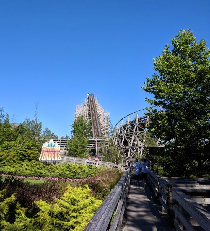 """Wooden roller coaster with a sign reading """"Shivering Timbers"""" and foliage in the foreground"""