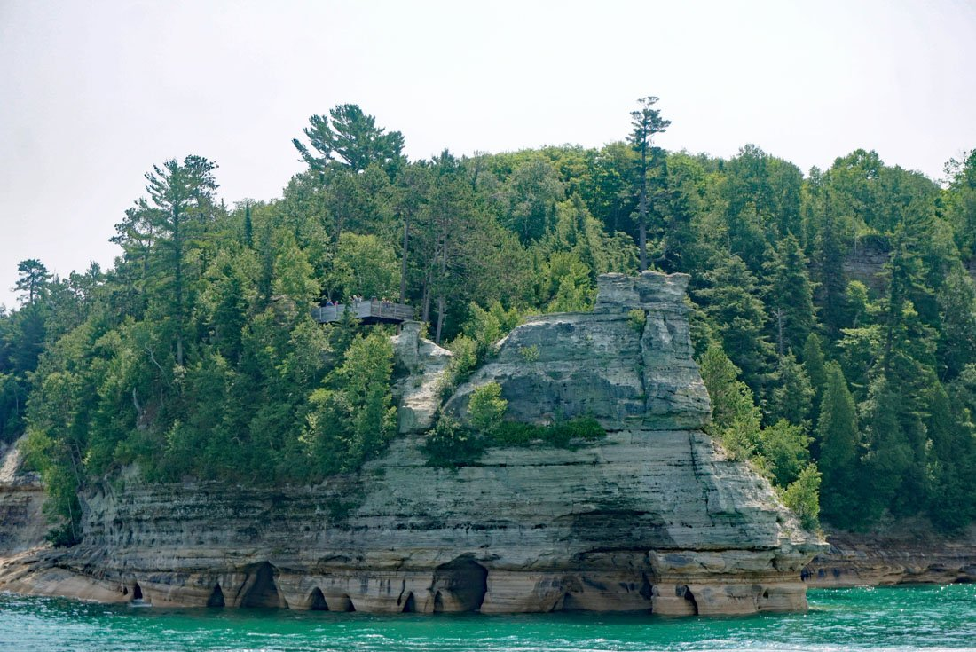 Tall rock formation known as Miners Castle with turrets towering above the turquoise waters of Lake Superior in Pictured Rocks National Lakeshore